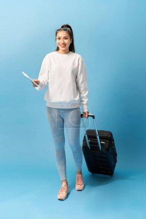 Photo pour Portrait de jeune fille tendance debout avec une valise et tenant un passeport avec des billets, sur fond bleu - image libre de droit