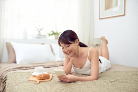 Young beautiful Asian woman lying on bed and using mobile phone with breakfast