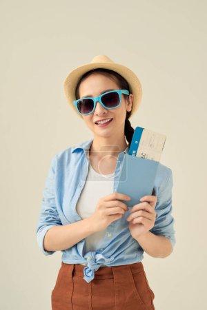 Porträt eines fröhlichen netten asiatischen Mädchen Reisenden zeigt Pass mit Tickets isoliert über grauem Hintergrund