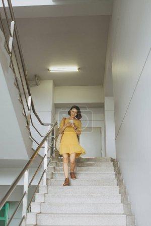 Photo pour Femme asiatique descendant les escaliers tout en utilisant smartphone . - image libre de droit