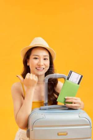 Photo for Concept of travel. happy woman girl with suitcase and passport on orange colored background - Royalty Free Image