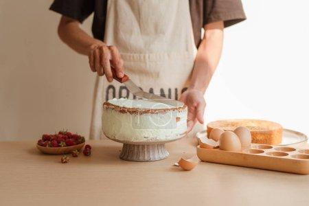 Putting the cream on top of sponge cake. Making sponge cake series