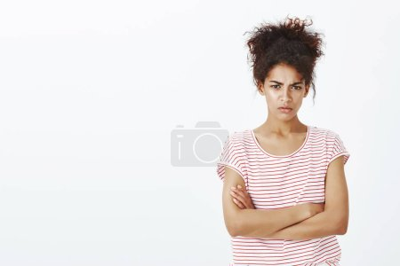 Not talking to you unless hear apology. Portrait of sulking cute dark-skinned woman in striped t-shirt, holding hands crossed on chest, looking from under forehead and frowning while being offended