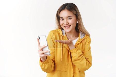 Photo pour Joyeuse charismatique blonde blonde asiatique fille porter élégant gilet sain d'oreilles sans fil veste jaune présenter nouvelle fonctionnalité smartphone recommander plate-forme impressionnante application de musique de téléphone souriant fond blanc ravi. - image libre de droit