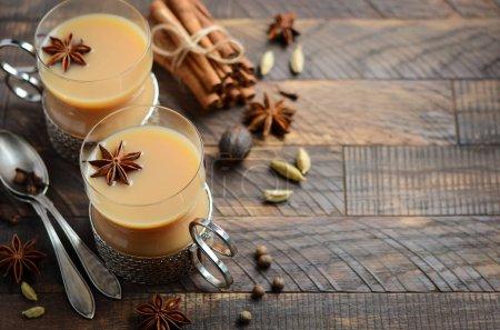 Thé indien masala chai. Thé épicé au lait dans une tasse vintage sur la table en bois rustique .