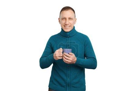 Foto de Hombre de edad media sonriente en suéter azul aislado sobre fondo blanco sosteniendo una taza de café azul . - Imagen libre de derechos