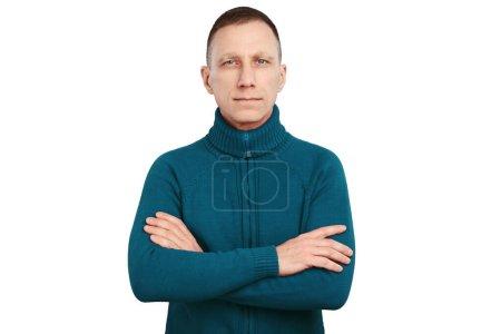 Foto de Hombre de edad media grave con brazos cruzados en suéter azul aislado sobre fondo blanco . - Imagen libre de derechos
