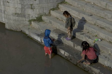 Children on the bank of the sacred river near the ...