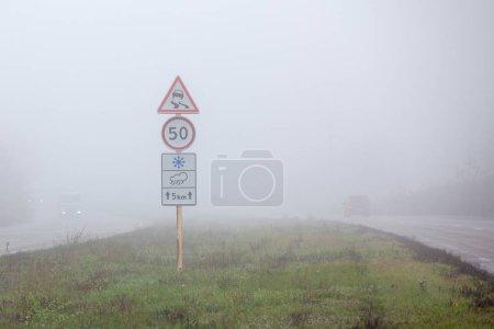 Photo pour Gros plan des panneaux d'avertissement sur une route brumeuse. Risque d'accident de la route et conditions météorologiques - image libre de droit
