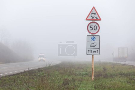 Photo pour Risque d'accident de la route et conditions météorologiques. Limite de vitesse et panneaux de signalisation glissants pendant la neige ou la pluie. Voiture d'ambulance sur une route brumeuse . - image libre de droit