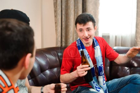 Friends cheering and drinking alcohol while watching soccer match on TV.