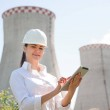Smiling engineer woman with tablet on electric sta...