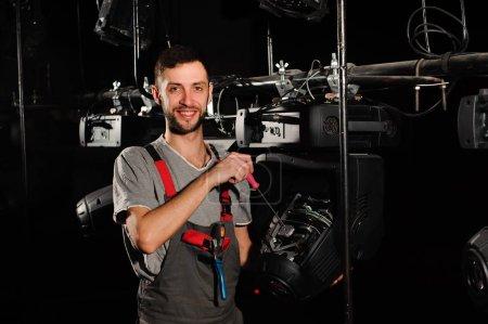"""Photo pour Le technicien d """"éclairage répare le dispositif lumineux sur scène - image libre de droit"""