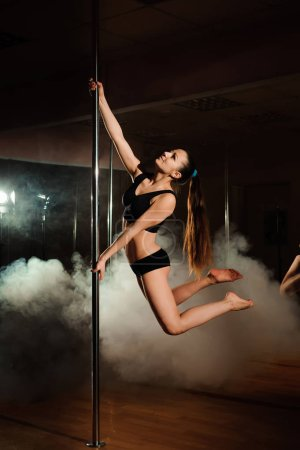 Photo for Beautiful slim girl with pylon. Female pole dancer woman dancing on a pole on a black background. - Royalty Free Image