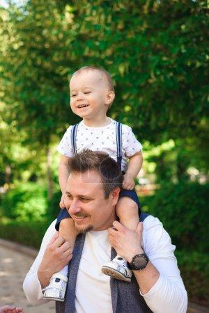 Photo pour Concept de famille, de parentalité, d'adoption et de personnes - mère heureuse, père et petit garçon marchant dans un parc d'été - image libre de droit
