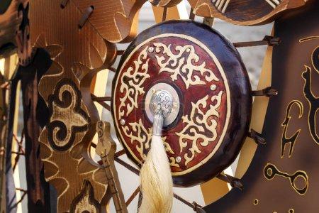 Photo pour Bouclier traditionnel d'un ancien guerrier asiatique avec une brosse en crin sur fond de symboles nationaux. Gros plan - image libre de droit