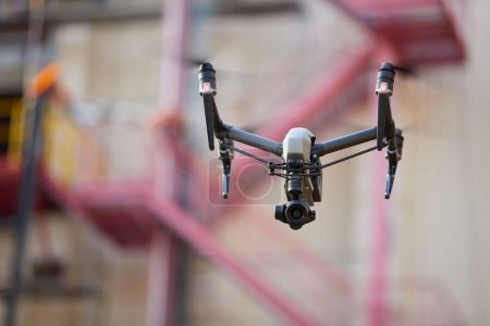 Photo for Hovering powerful black quadcopter with camera against blurred industrial construction. Visual inspection of hard to reach objects from the air in the industry. Front view. - Royalty Free Image