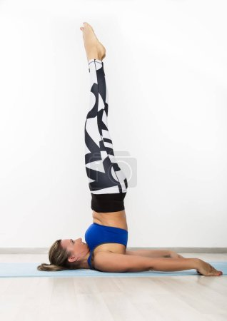 Sporty young woman practice yoga asana in class. C...