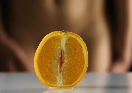 Photo pour Close-up demi-orange, femme enlève sa culotte sur un fond sombre. vagin imitation - image libre de droit