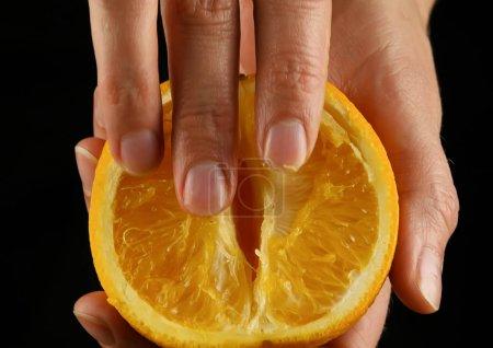 Photo pour Gros plan femelle main caressant les fruits orange, empreinte d'une caresse. imitation sexe - image libre de droit