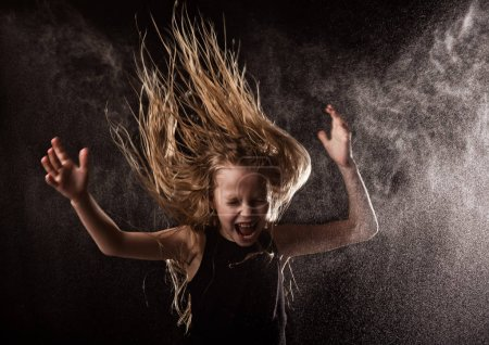 Photo for Young girl with live emotions dancing under water drops. child splashing water on a dark background. - Royalty Free Image