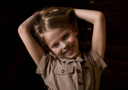 Photo for Beautiful lovely little blonde girl with different emotions on a dark background - Royalty Free Image