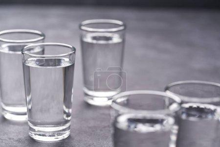 Foto de Vodka ruso sobre mesa negra, enfoque selectivo.Vodka en vasos de chupito sobre fondo negro - Imagen libre de derechos