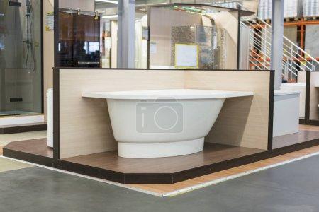 Photo pour Bain blanc dans la Banque de construction. bains dans le magasin de plomberie. Boutique de génie sanitaire. Salle de bains blanche. Baignoire de coin dans le magasin de bâtiment. - image libre de droit