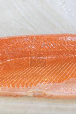 Filet de saumon dans la glace sur le comptoir du supermarché. Filet de poisson rouge dans la glace au supermarché. Aliments marins sains. photo verticale .