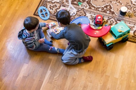 Two little brothers play in the game room with car...
