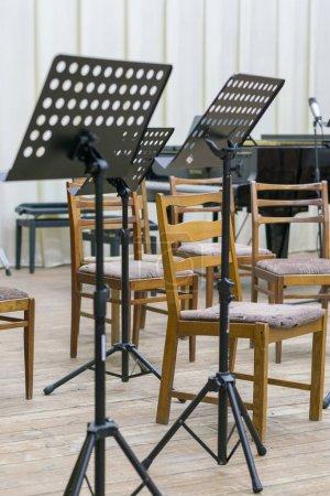 Photo pour Sièges vides et quelques instruments dans le music-hall en attendant l'arrivée de l'orchestre sur scène. stand de musique noire sur scène - image libre de droit