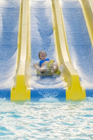 Photo pour Amusant sous le soleil jolie fille en bikini descend chute d'eau dans la piscine. Belle fille chevauchant un toboggan aquatique. femme heureuse descendant sur l'anneau en caoutchouc. photo verticale - image libre de droit