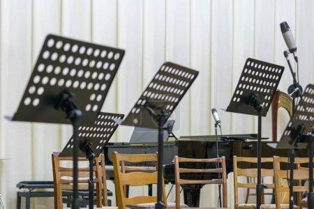 Photo pour Sièges vides et quelques instruments dans le music-hall en attendant l'arrivée de l'orchestre sur scène. stand de musique noire sur scène . - image libre de droit