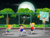 Happy boys playing basketball at the court in night