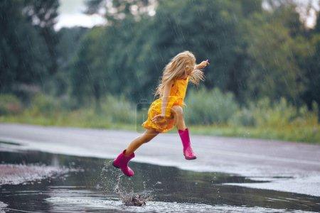 ein kleines Mädchen in einem gelben Kleid lächelt und rennt durch den Pudding