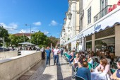 Lisbon, Portugal - May 9th 2018 - Tourists and locals walking in a traditional pathway in Lisbon downtown, restaurants and trees in Portugal.