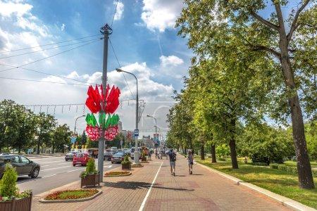 Photo pour Minsk, Belarus, 28 juin 2018 - touristes et des habitants marchant dans un pavé large avec grands arbres et de voitures dans l'avenue à Minsk en Biélorussie - image libre de droit