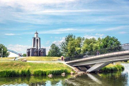 Photo pour Minsk (Bélarus), 28 juin 2018 - un pont reliant une petite île avec un temple un arbres verts dans une journée de ciel bleu à Minsk - image libre de droit