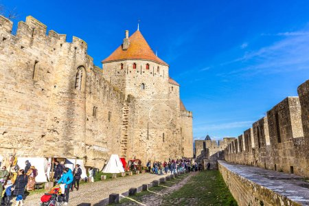 Photo for Carcassonne, France - Dez 11th 2017 - Big group of tourist inside in the castle of Carcassonne in a blue sky day in France - Royalty Free Image