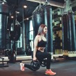 Training legs in the gym. Attractive fit woman doi...