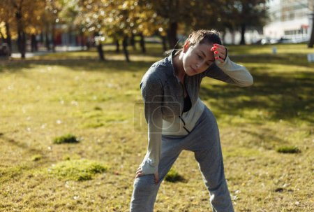 Photo for Outdoor workout concept. Tired sport woman in sport clothes wipes sweat from her forehead with her sleeve in the autumn park - Royalty Free Image