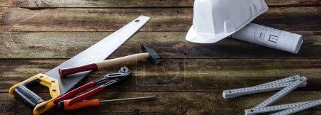 Photo pour Bannière d'outillage de maison pour la construction, l'entretien, l'artisanat et la réparation avec un chapeau dur, un imprimé bleu architecte et des outils de menuiserie sur fond en bois - image libre de droit