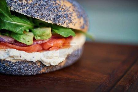 Photo pour Gros plan d'un bagel graines de délicieux fromage saumon et crème de pavot avec légumes reposant sur une planche à servir sur une table rustique de bois turquoise - image libre de droit