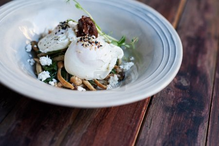 Photo for Two delicious poached eggs over fried mushrooms, feta and mixed greens in a bowl on a rustic wooden table - Royalty Free Image