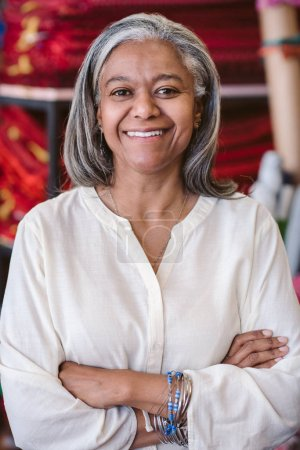 Portrait of a smiling mature fabric shop owner standing with her arms crossed by shelves of colorful cloths and textiles