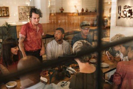 Photo pour Serveur souriant parlant avec un groupe de jeunes amis souriants dégustant un repas ensemble à une table dans un bistrot - image libre de droit