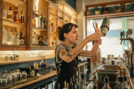 Photo for Young female bartender standing behind the counter of a trendy bar using a shaker to make cocktails - Royalty Free Image