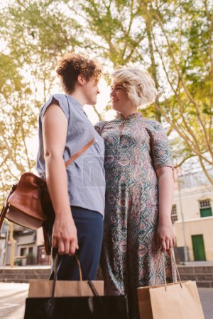 Smiling young lesbian couple standing on a street ...