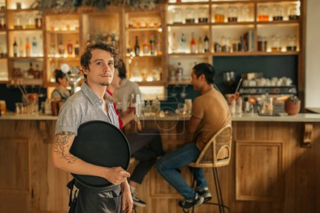 Portrait of a young waiter holding a tray while standing in a trendy bar with customers in the background
