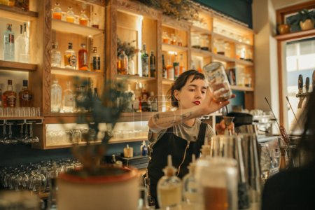 Photo for Young female bartender standing behind the counter of a trendy bar measuring alcohol while making cocktails for customers - Royalty Free Image